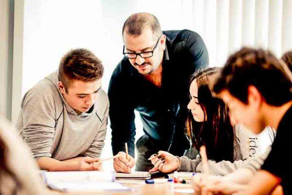 Öğretmen öğrencilerle bire bir anlatımla ders yapıyor.
